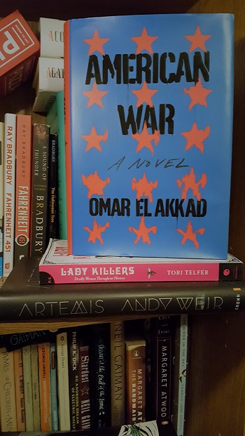 A copy of American War by Omar El Akkad on a bookcase.